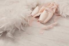 Różowi baletniczy pointe buty, piórko na białym drewnianym tle i Obrazy Royalty Free