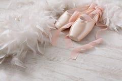 Różowi baletniczy pointe buty, piórko na białym drewnianym tle i Zdjęcie Stock