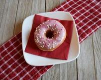 Różowi frosted pączek na talerzu z czerwoną pieluchą zdjęcie royalty free