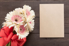 Różowi gerbera kwiaty, karta i są w drewnianym tle z faborkiem Obrazy Royalty Free
