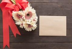 Różowi gerbera kwiaty, karta i są w drewnianym tle z faborkiem Obrazy Stock