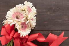 Różowi gerbera kwiaty są w drewnianym tle z faborkiem Obraz Stock