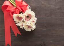 Różowi gerbera kwiaty są w drewnianym tle z faborkiem Fotografia Stock