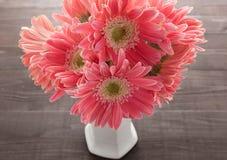 Różowi gerbera kwiaty są w wazie, na drewnianym tle Fotografia Royalty Free