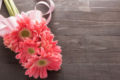 Różowi gerbera kwiaty z faborkiem są na drewnianym tle Obrazy Stock