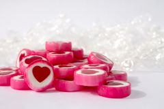 Różowi i biali candys z czerwonymi sercami na białym tle obrazy stock