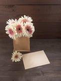Różowi i biali gerbera kwiaty są w torbie na drewnianym tle z kartą, Obraz Stock