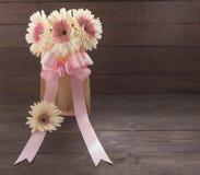 Różowi i biali gerbera kwiaty z faborkiem są w torbie na drewnianym tle, Obrazy Stock