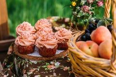 Różowi muffins, świeża owoc i wildflowers skład, obraz royalty free