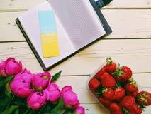 różowi peonia kwiaty, truskawkowe jagody i notatnik na białym tle, Zdjęcie Royalty Free