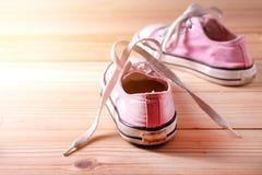 Różowi sneakers na drewnianej podłoga Fotografia Royalty Free