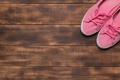 Różowi sneakers na drewnianym tle zdjęcia stock
