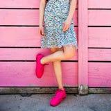 Różowi sneakers na dziewczyn nogach na grunge drewnianych menchiach izolują tło Ulica styl Dziewczyna jest ubranym sneakers i lat Zdjęcia Stock