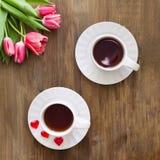 Różowi tulipany na drewnianym tle, dwa filiżanki herbata i kawa na spodeczkach z sercami marmoladowymi, Zdjęcia Stock