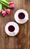 Różowi tulipany na drewnianym tle, dwa filiżanki herbata i kawa na spodeczkach z sercami marmoladowymi, Fotografia Stock