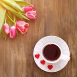 Różowi tulipany na drewnianym tle, dwa filiżanki herbata i kawa na spodeczkach z sercami marmoladowymi, Zdjęcie Stock