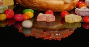 Różowy śmieszny zdziwiony oszklony pączek z kropi, paskował karmel cukierki, kolorowego dragee z rodzynkami lub arachidy zbiory wideo
