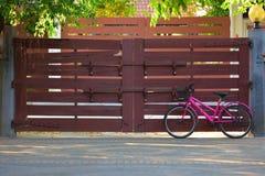 Różowy bicykl z Drewnianą bramą na tle Fotografia Stock