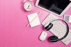 Różowy biurowego biurka stół z komputerem, bezprzewodowy hełmofon, alarmowy cl zdjęcie stock
