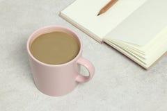 Różowy filiżanka kawy, otwierająca książka i ołówek na granitowej teksturze, zdjęcie stock