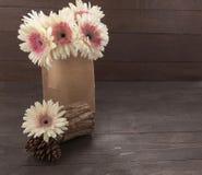 Różowy i biali gerbera szalunek i kwiaty są na drewnianym tle z torbą Fotografia Stock