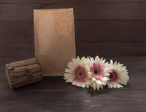 Różowy i biali gerbera szalunek i kwiaty są na drewnianym tle z torbą Obraz Stock