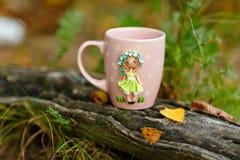 Różowy kubek z dekoracjami w postaci dziewczyny w sukni robić Obrazy Royalty Free