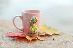 Różowy kubek z dekoracjami w postaci dziewczyny w sukni robić Fotografia Stock