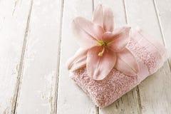 Różowy leluja kwiat i miękka część ręcznik na drewnianym tle Zdjęcia Stock