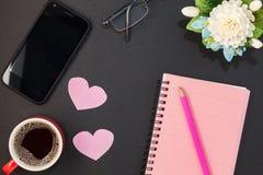 Różowy notatnika papier z ołówkiem, smartphone i filiżanką na bla, Obrazy Royalty Free