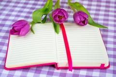 Różowy notepad z prążkowanym papierem i trzy purpurowymi tulipanami na białym purpurowym w kratkę tekstylnym tle Romantyczna kart zdjęcia royalty free