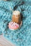 Różowy pączek z marshmallow i gorąca czekolada w szklanej filiżance na błękitnych merynosach dziamy koc Światła na tle fotografia royalty free