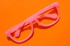 Różowy plastick eyeglasses kłamstwo na pomarańczowym tle ?mieszny modnisia poj?cie obrazy royalty free