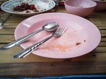 Różowy plastikowy naczynie, łyżka i rozwidlenie stal, jesteśmy stołowi drewniani z kopii przestrzenią Zdjęcia Royalty Free