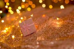 Różowy prezent na koralowym tle z zamazanymi światłami girlanda fotografia royalty free