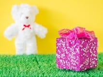 Różowy prezenta pudełko na zielonym sztucznym szkle i rozmytym białym niedźwiedziu Zdjęcia Stock