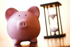 Różowy prosiątko bank z rocznika hourglass behind Obrazy Royalty Free