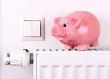 Różowy prosiątko banka skok, ratujący elektryczność i grzejnych koszty Zdjęcia Royalty Free