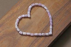Różowy serce na drewnianym tle Kunzite jest naturalnym menchii kamieniem dla tworzyć biżuterię Naturalni kryształy menchie i bzów obraz royalty free