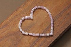 Różowy serce na drewnianym tle Kunzite jest naturalnym menchii kamieniem dla tworzyć biżuterię Naturalni kryształy menchie i bzów zdjęcia stock