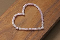 Różowy serce na drewnianym tle Kunzite jest naturalnym menchii kamieniem dla tworzyć biżuterię Naturalni kryształy menchie i bzów obrazy royalty free