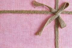 Różowy tło z burlap łękiem i faborkiem obraz royalty free