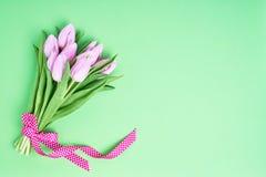 Różowy tulipanu bukiet dekorował z faborkiem na zielonym tle kosmos kopii Obraz Stock
