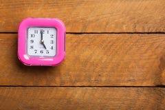 Różowy zegar na drewnianym tle Zdjęcia Stock