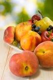 Różne owoc na talerzu na zamazanym tle Fotografia Stock