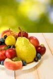 Różne owoc na talerzu na zamazanym tle Zdjęcia Royalty Free