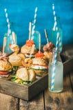 Różni domowej roboty hamburgery z kijami w drewnianej tacy i lemoniadzie Zdjęcie Stock