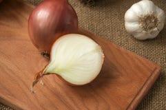 Różnorodne cebule na desce grabije na tle, burlap Zdjęcie Stock