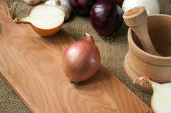 Różnorodne cebule na desce grabije na tle, burlap Obraz Stock