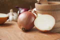 Różnorodne cebule na desce grabije na tle, burlap Zdjęcia Stock